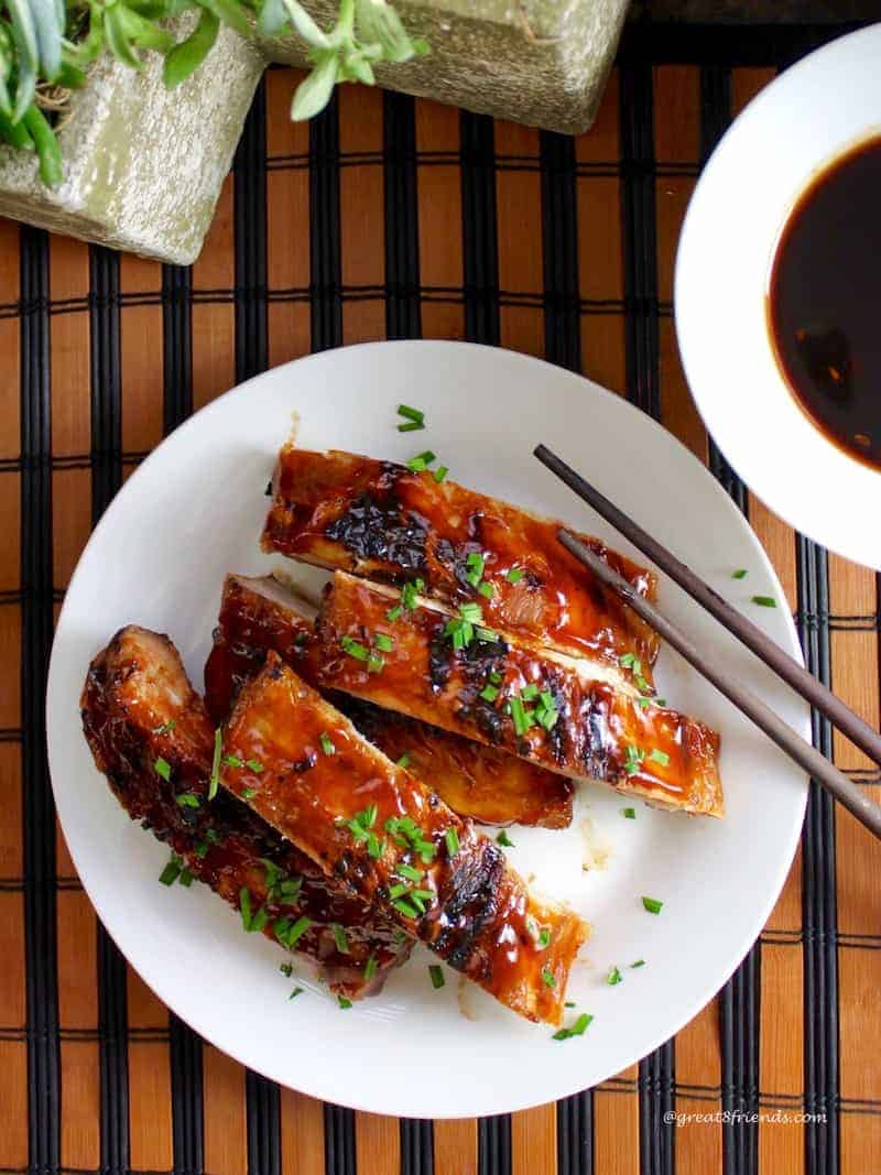 Overhead shot of Chinese style ribs stacked on a white plate with extra sauce.