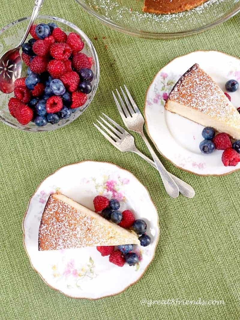 Overhead shot of 2 plates each with a slice of ricotta cake with berries. There are 2 forks in the center and a bowl of berries off to the side.