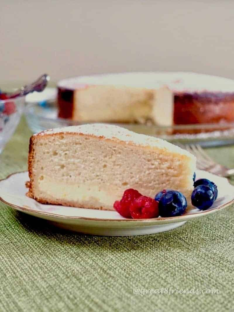 A slice of cake on a plate with berries. The larger cake is blurry in the background.