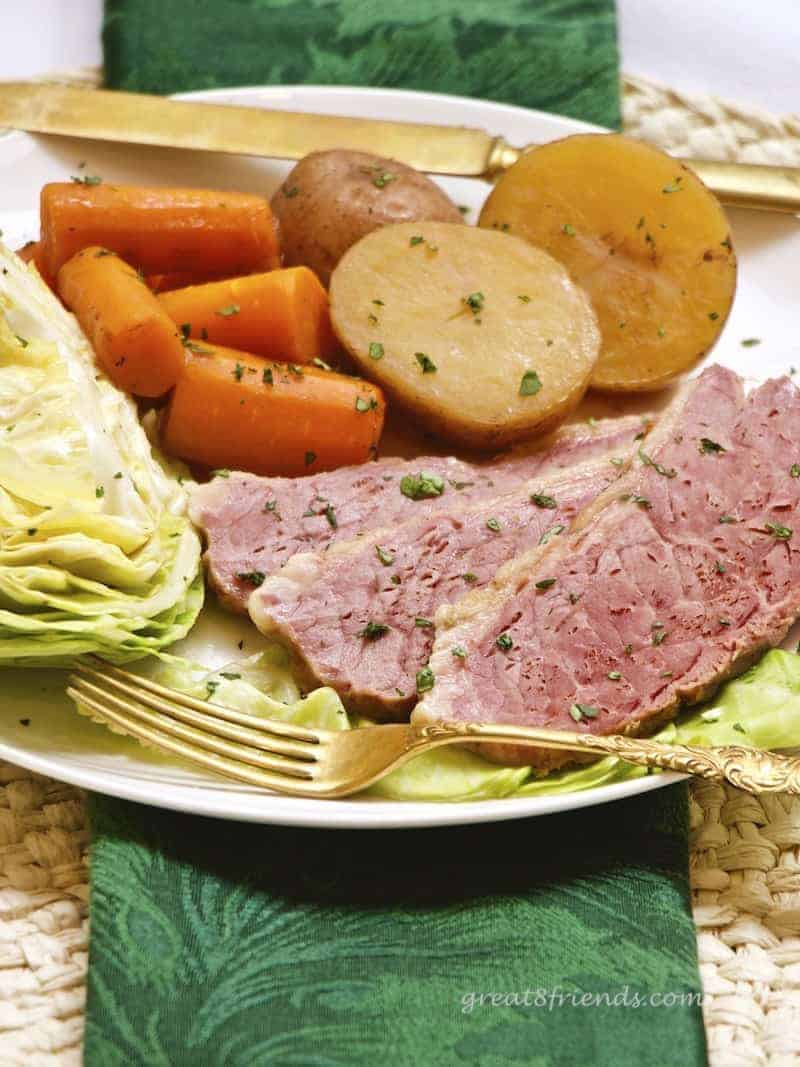 Corned Beef and cabbage with potatoes and carrots on a plate.