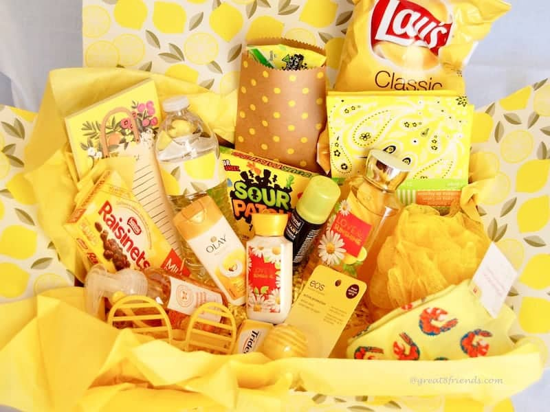 A yellow box filled with yellow tissue paper and yellow items, Lays potato chips, raisinets, olay cream, yellow sour patch kids, yellow note pad, etc.