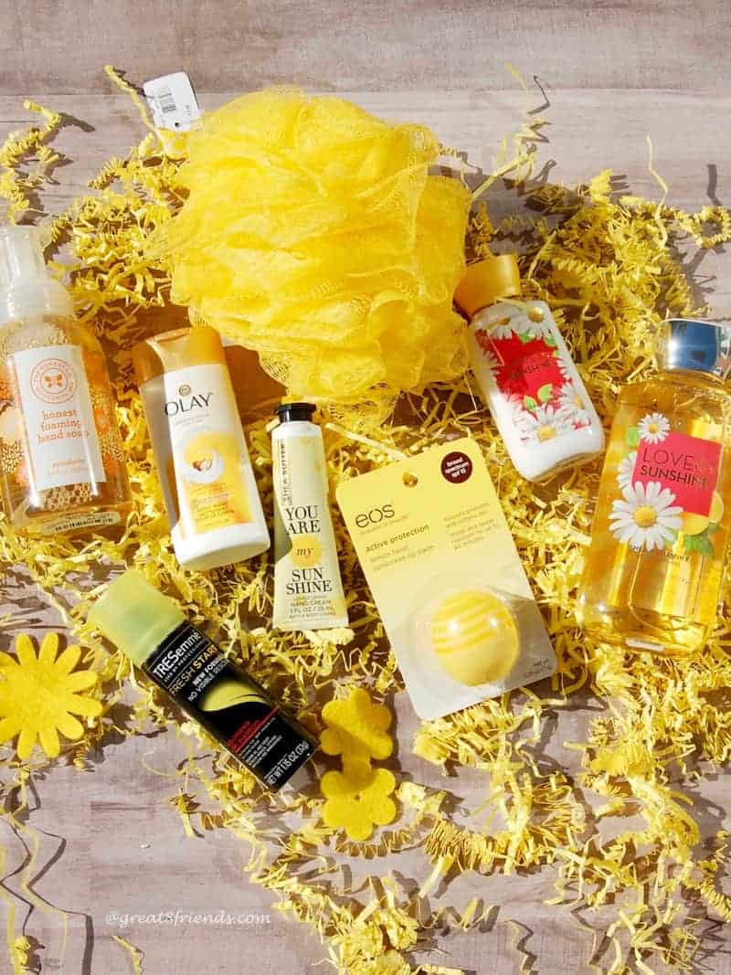 Yellow loofah, and various yellow body products laying on yellow shred.