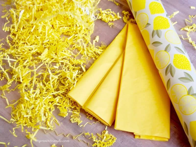 Yellow shred, yellow tissue and a roll of wrapping paper with lemons on it.
