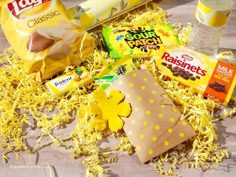 Yellow packaged snacks laying on yellow shred.