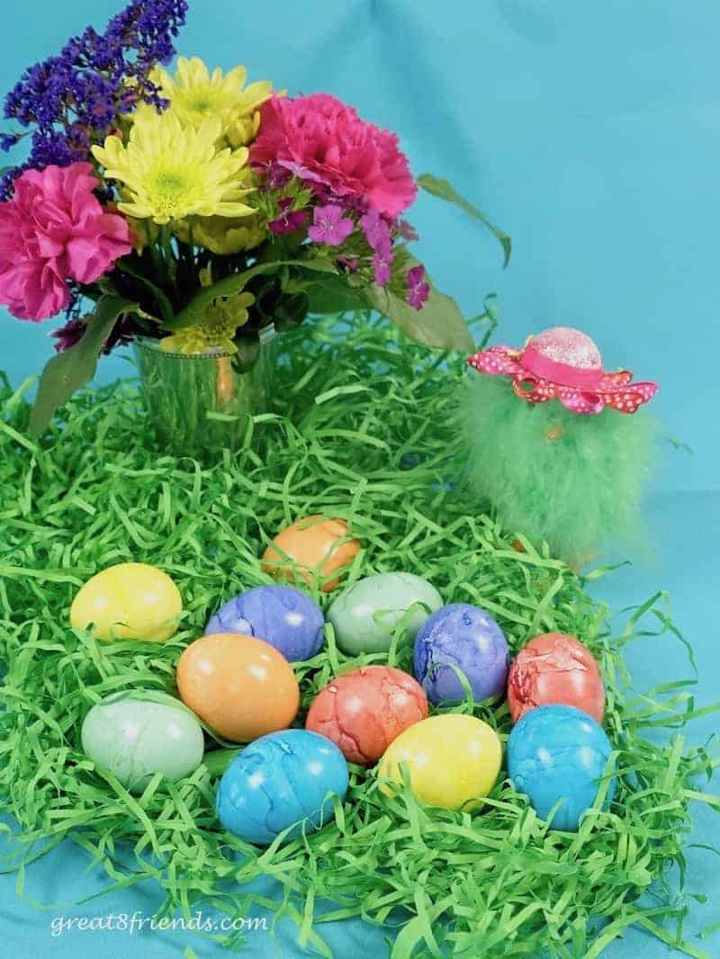 Spring Flower arrangement with green Easter grass, colorful dyed eggs, and a furry chick wearing a pink hat.