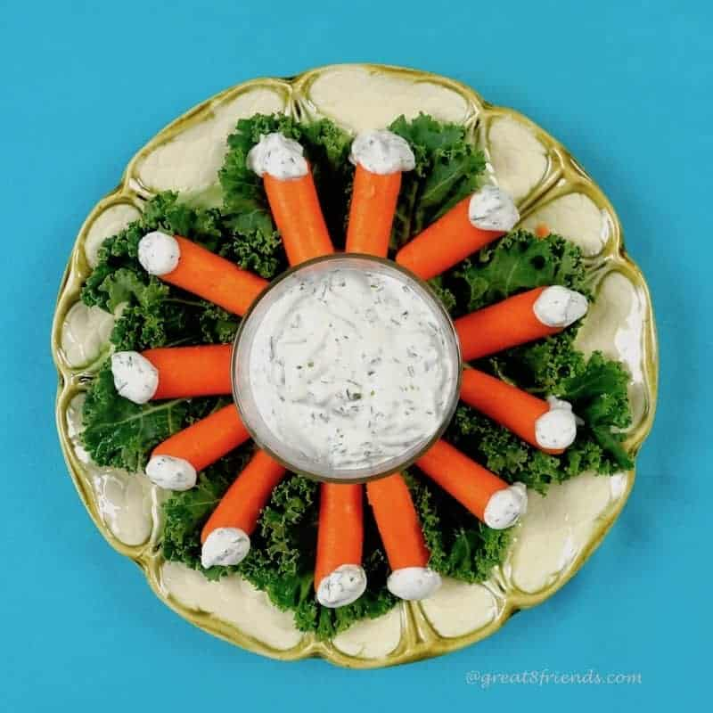 "Herby Dill Dip in the center of a plate surrounded with baby carrots each pointing in to the dip each with a dollop of dip for a ""tail."""