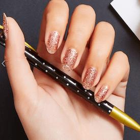 Manicured glitter fingernails on a hand holding a pen.