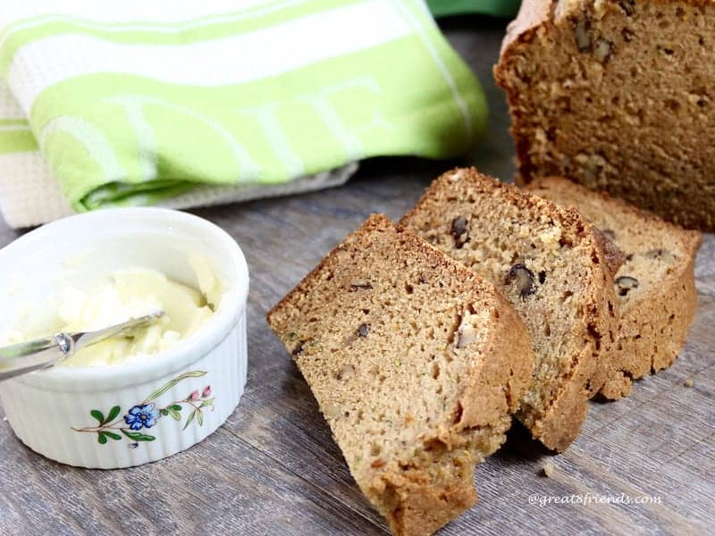 Three slices of zucchini bread and a bowl of butter.