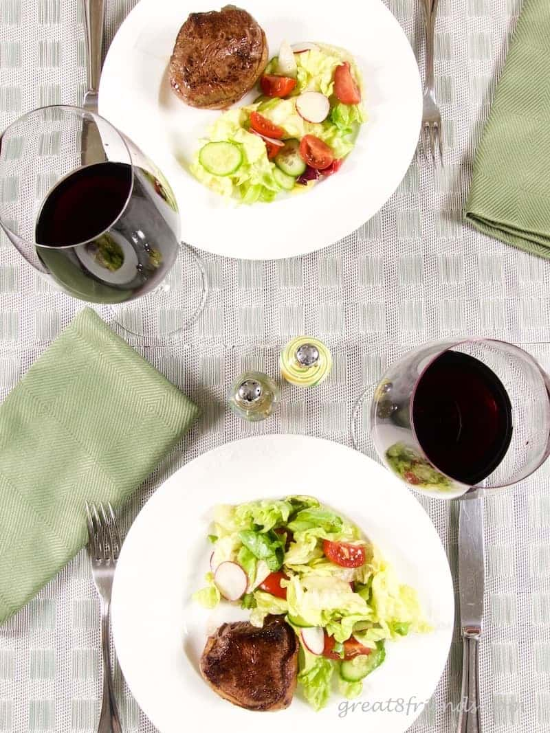 Overhead shot of table setting with wine and steaks and salad.