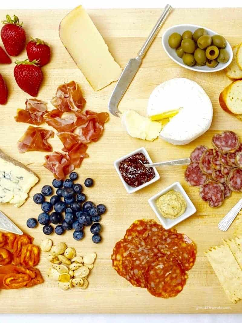A Cheese and Charcuterie Board including fruit, nuts, crackers, olives and bread slices.