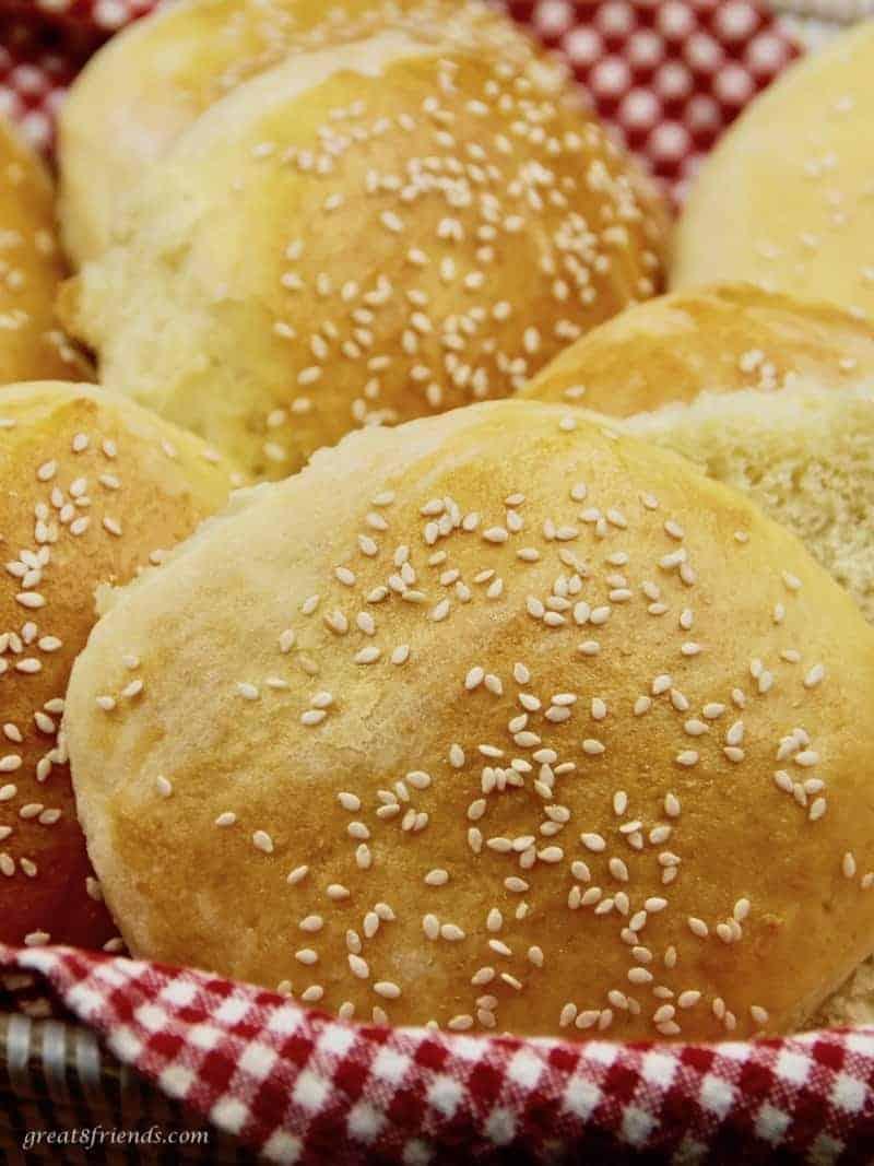 Several homemade sesame seed hamburger buns in a basket.