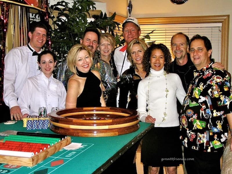 People posing for a photo in front of a roulette table.