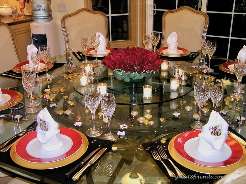 A round table set for a Las Vegas Dinner Party with a centerpiece of red roses surrounded by votive candles. foil wrapped chocolates are on the table and the plates are red rimmed sitting on gold chargers.