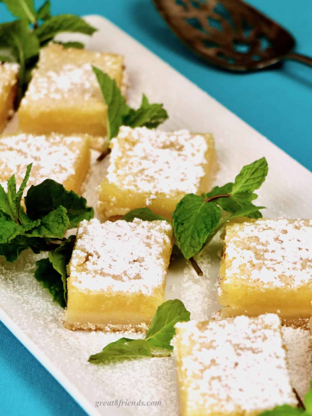 Lemon bars on white tray garnished with mint leaves.