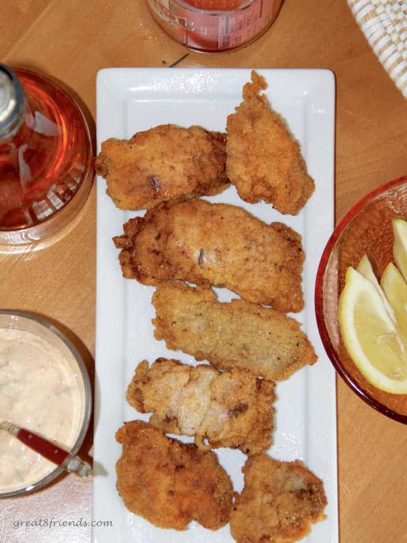 Overhead shot of fried catfish with a sauce and lemon wedges on the side.