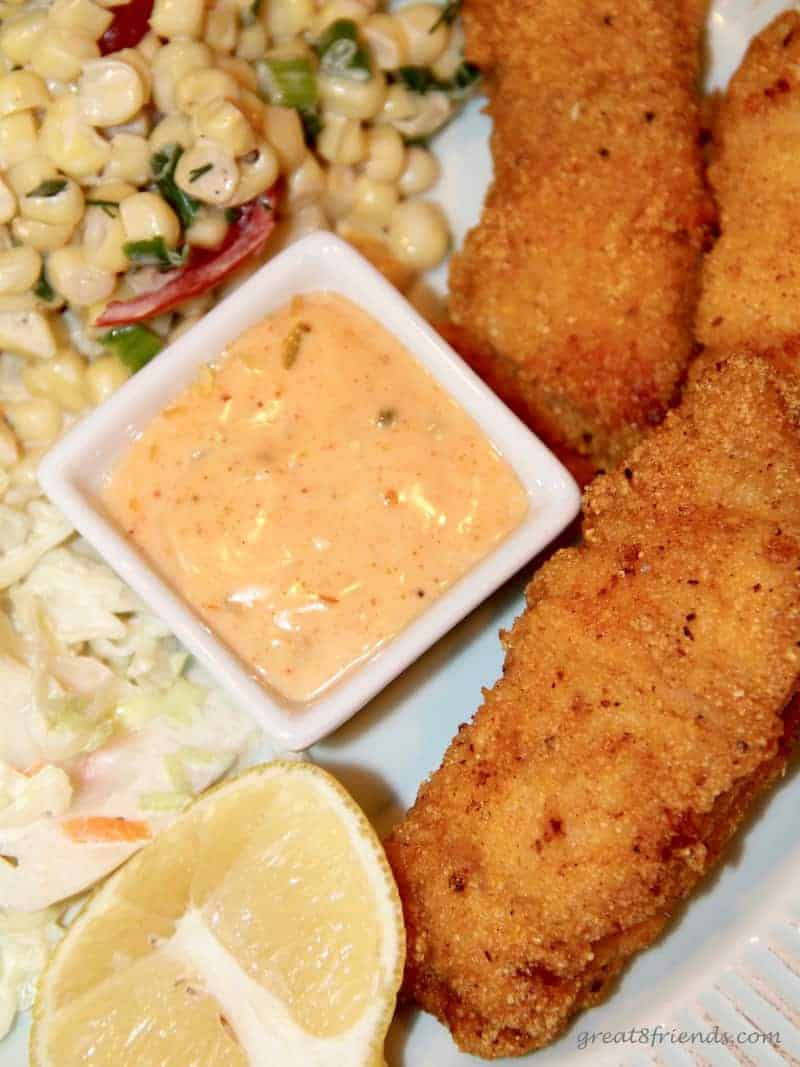 Spicy classic pan fried catfish pieces served as an appetizer with a spicy tarter sauce and corn salad on the side.