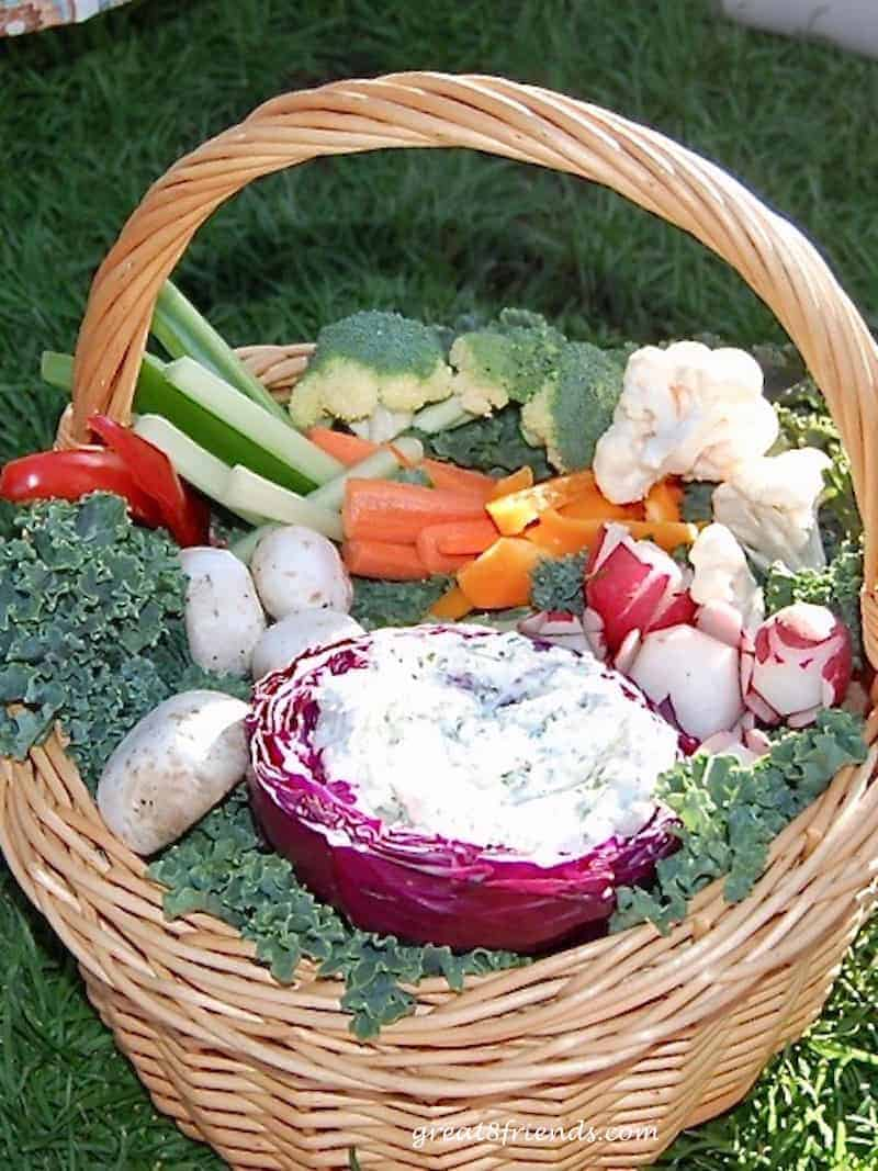 Baskeet of fresh cut vegetables with a dip in a carved out red cabbage.