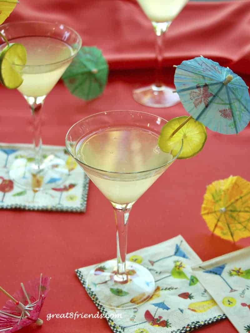 3 rum daiquiris in martini glasses garnished with lime rounds and paper umbrellas on a coral background.
