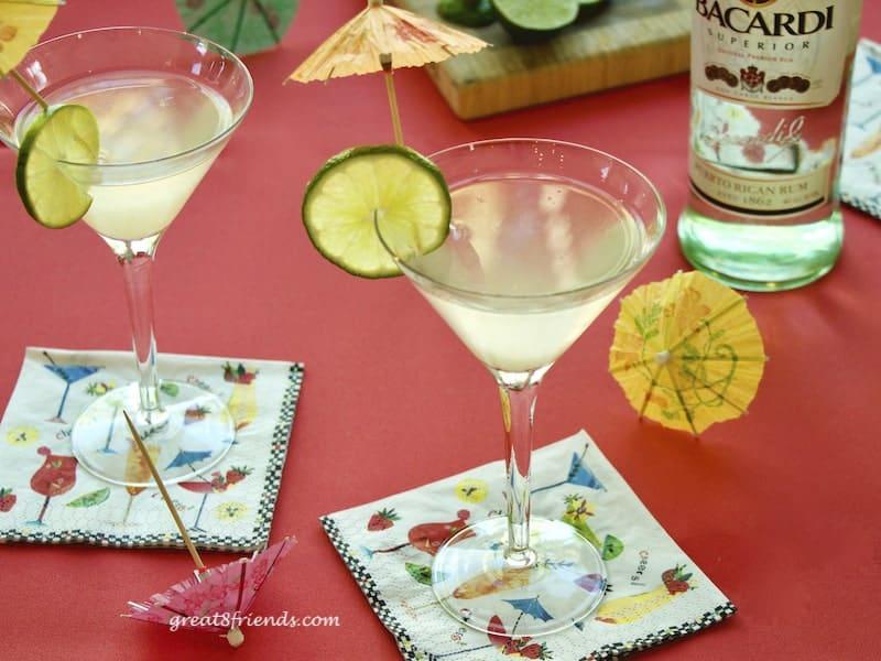 2 glasses of Original Rum Daiquiri with umbrellas and limes.