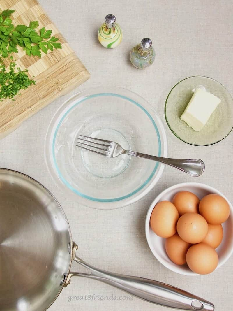 The ingredients for an omelette. A bowl, a fork, salt and pepper, butter, eggs, parsley and a pan.