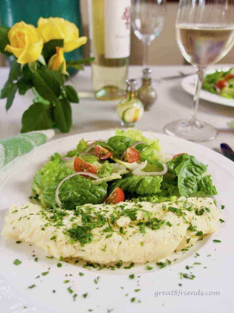 An omelette roulée with a small salad a glass of white wine and some yellow roses.