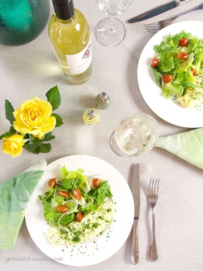 Overhead shot of table set with yellow roses, white wine and two plates of omelettes and salad.