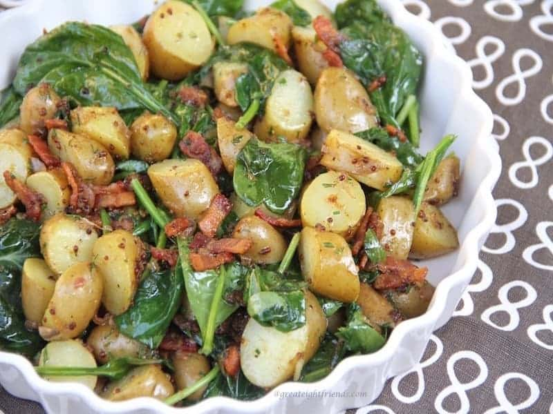 Warm Spinach Potato Salad with Bacon Vinaigrette on a brown Great 8 napkin.