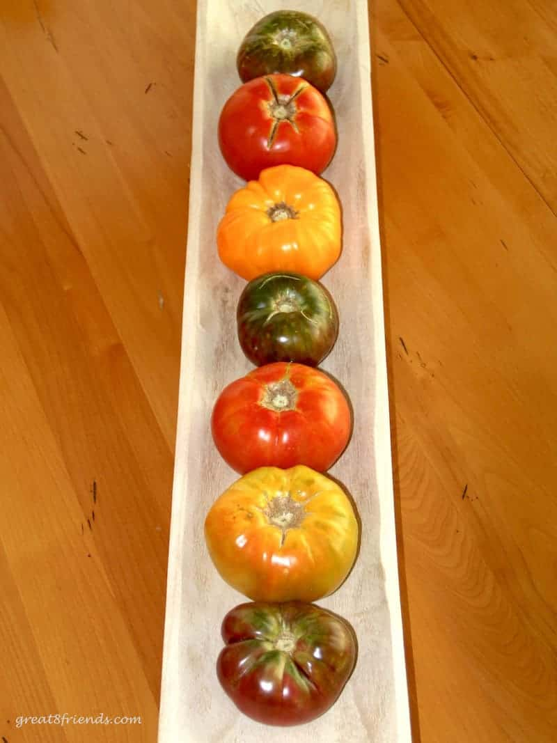 Heirloom tomatoes lined up vertically in a wood long bowl on a wood table.
