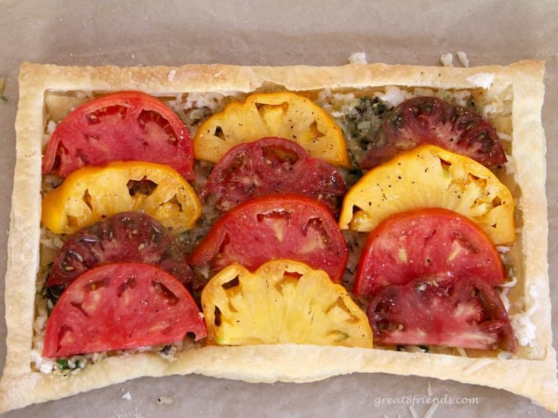 heirloom tomatoes on top of cooked onions on a baked puff pastry sheet.