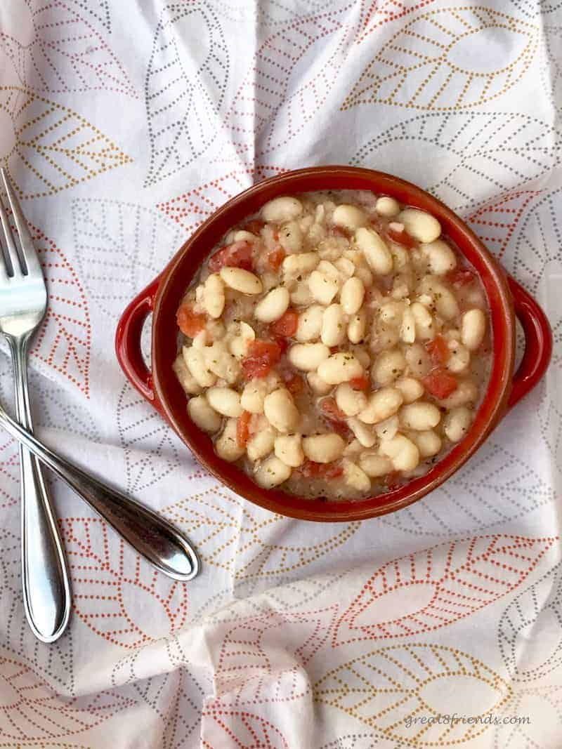 Overhead shot of the white beans and tomatoes in a round red bowl with a fork on one side.