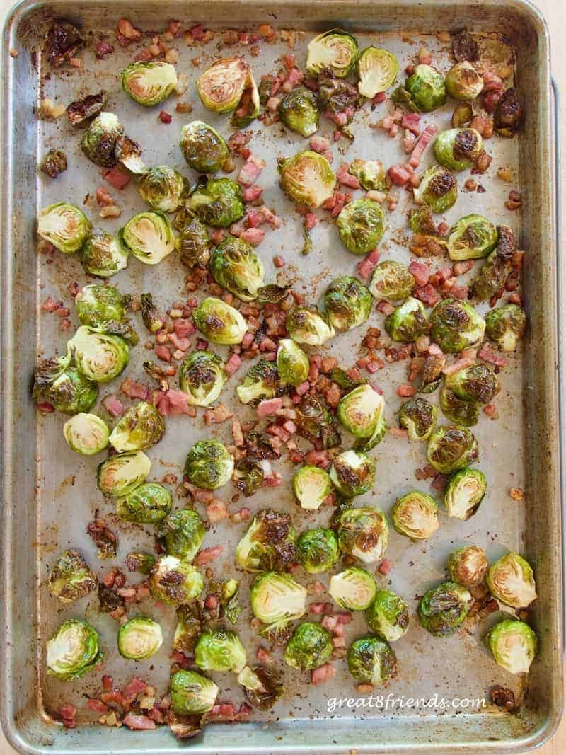 Overhead shot of halved brussels sprouts on a sheet pan tossed with pancetta pieces.