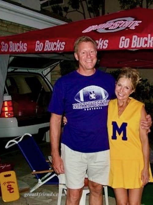Man in a Northwestern shirt and woman in a Michigan cheer uniform.