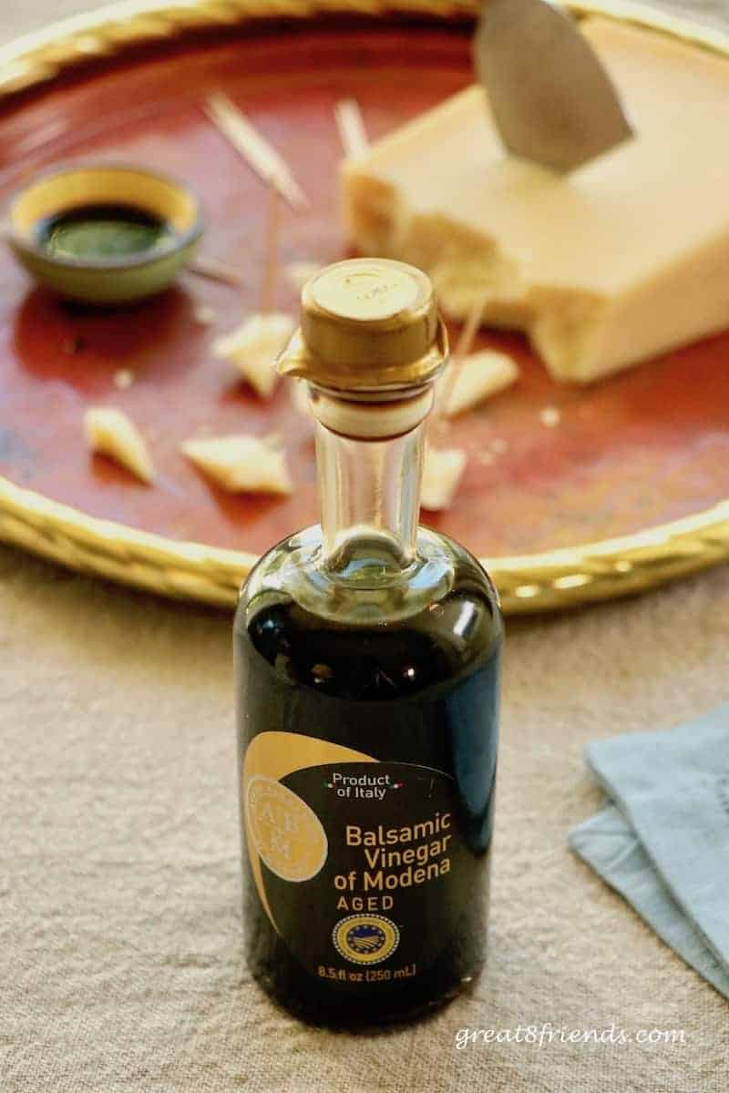 Bottle of balsamic vinegar with cheese in the background.