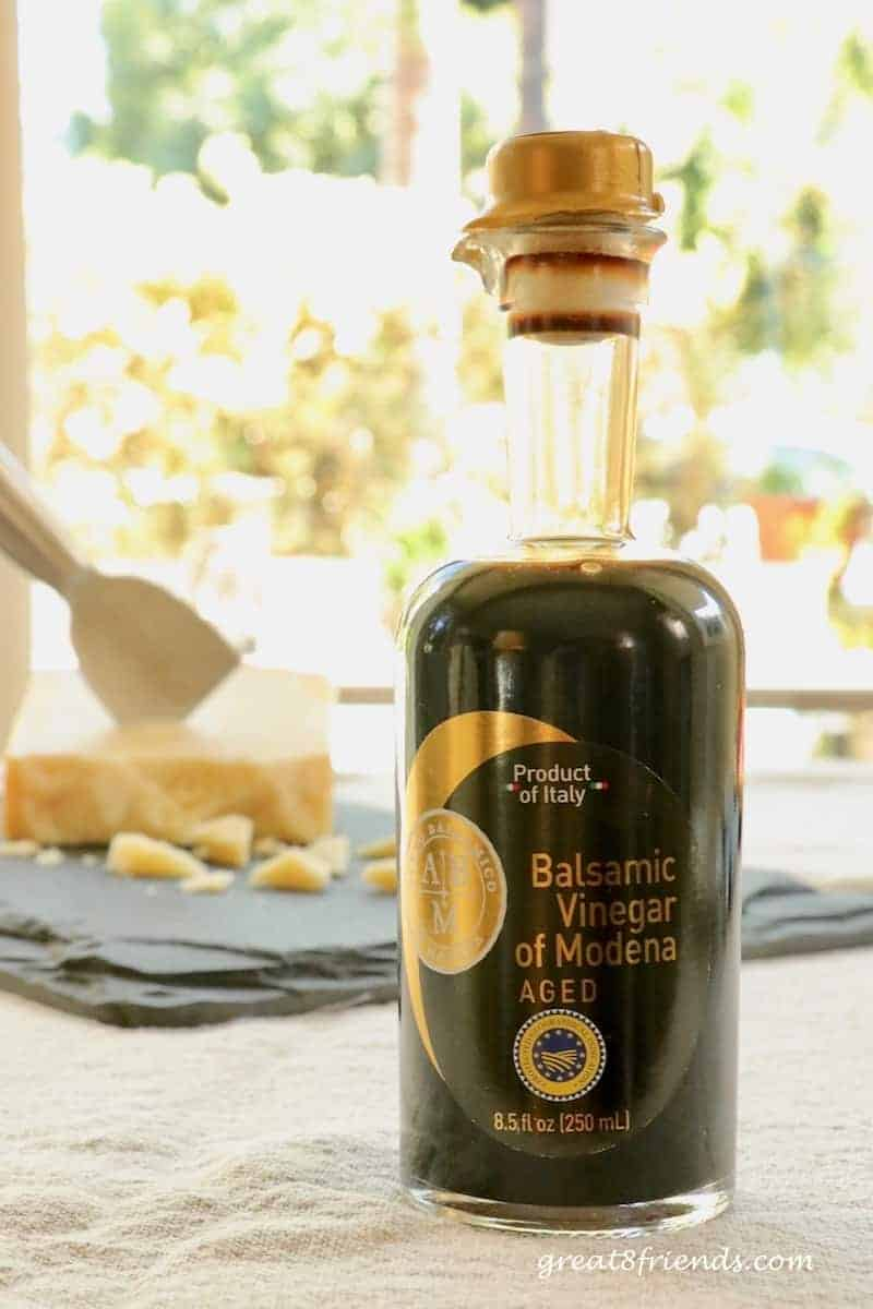 A bottle of Balsamic Vinegar of Modena with a hunk of Parmigiano Reggiano in the background.