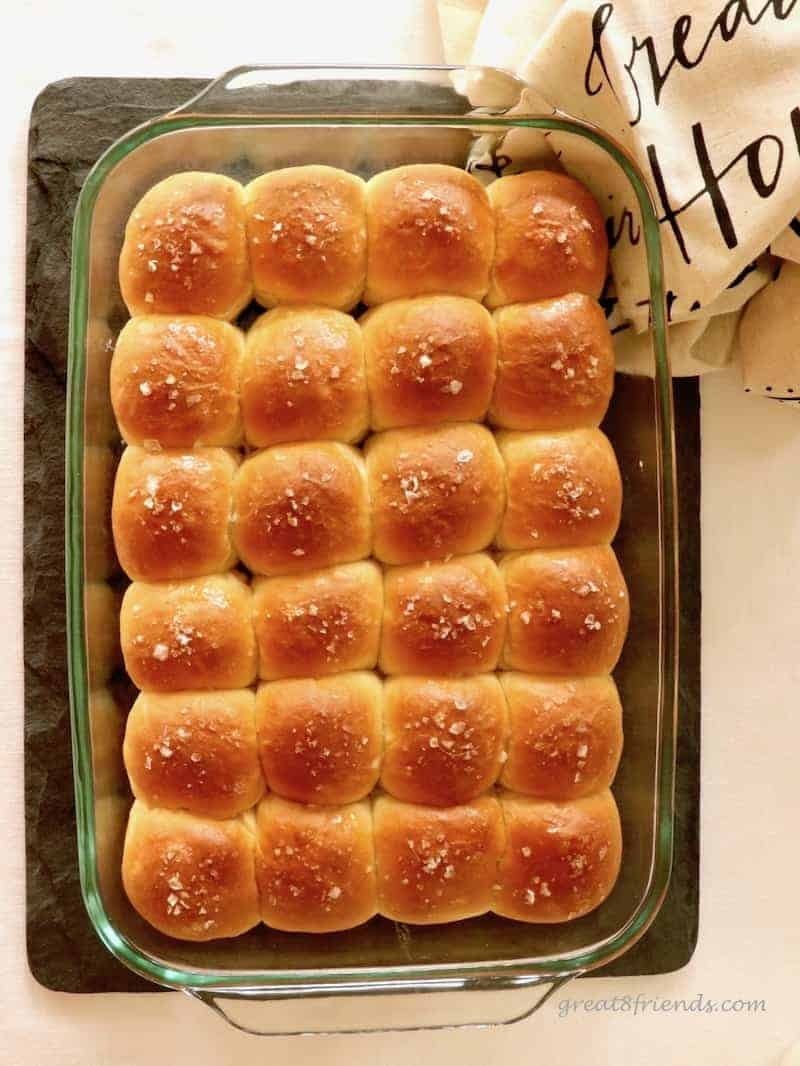 Overhead shot of a 9x13 glass dish with dinner rolls sprinkled with salt.