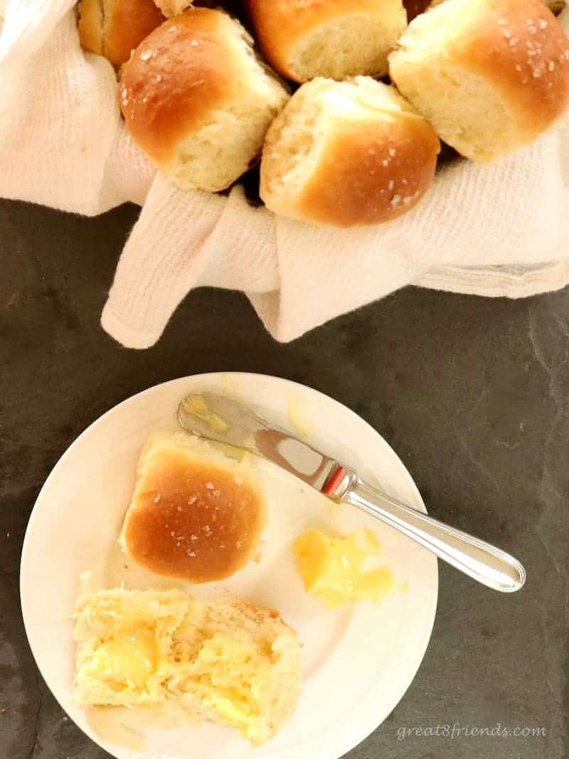 A dinner roll cut in half on a plate with some butter and the basket of rolls.