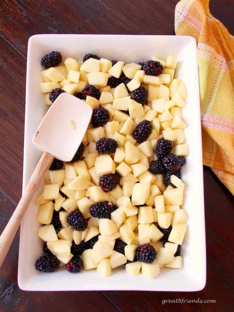 Raw cubed apple pieces and blackberries in a baking dish.