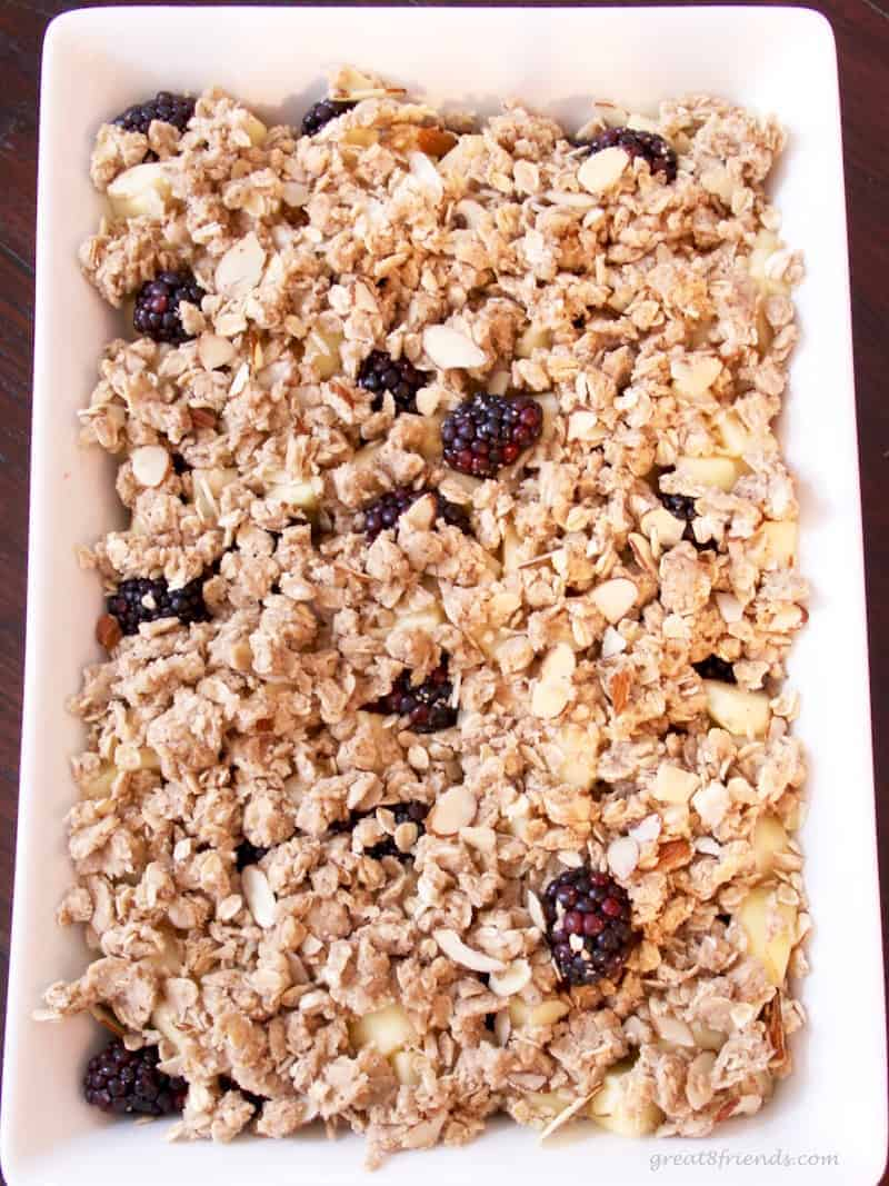 Apples and Blackberries in a baking pan with the streusel ready for baking.