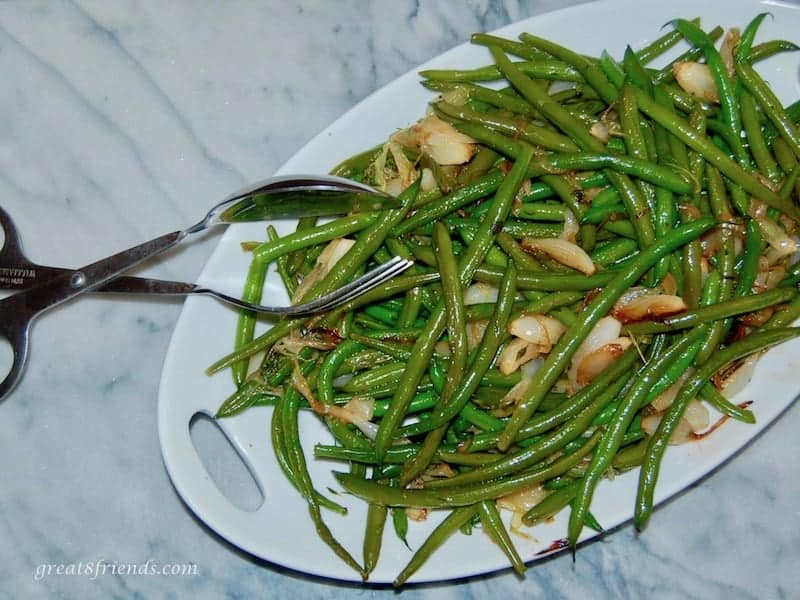Overhead shot of green beans and onions on a white platter. with tongs to serve.