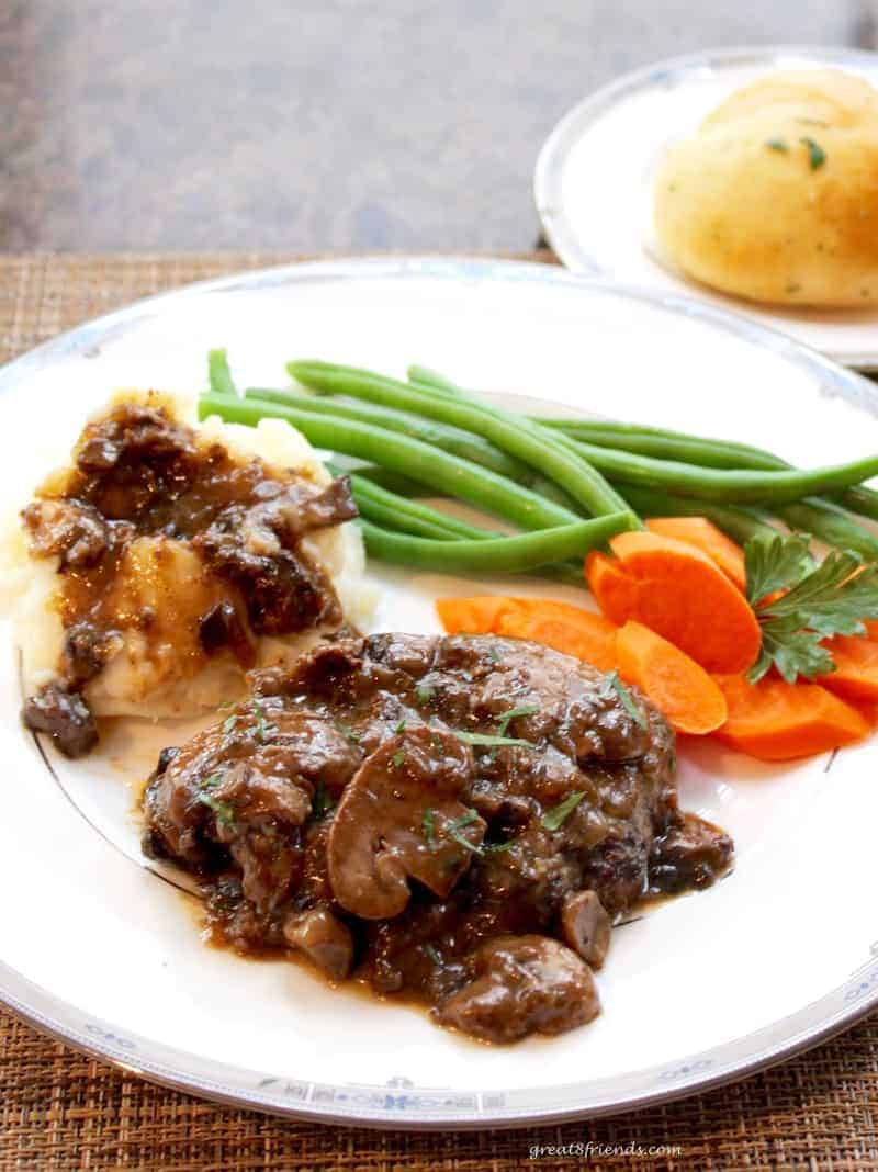 Salisbury Steak with Mushroom Onion Gravy served with carrots and green beans and a roll.