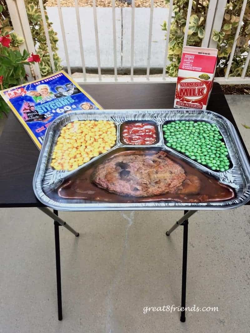 A tv tray with fake tv dinner, mocked up TV guide and carton of milk.
