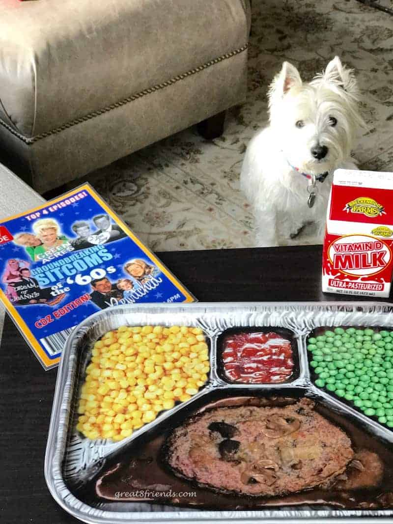 TV tray with fake tv dinner, a carton of milk and invitation, with a white dog in the background.