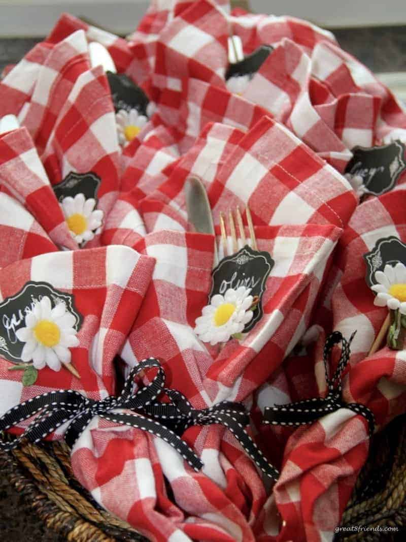 Red and white napkins wrapped around utensils with a daisy.