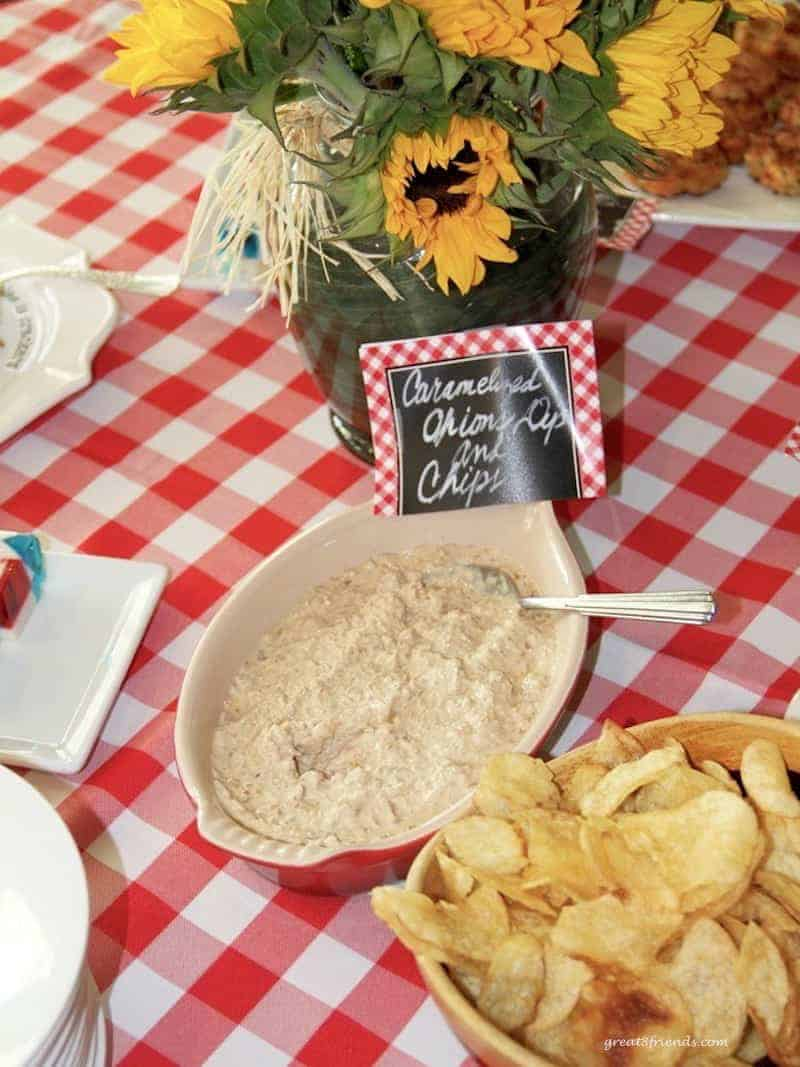 Onion dip and potato chips on red and white checked tablecloth.
