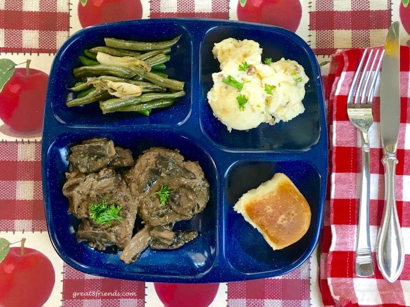 Blue divided plate with salisbury steak, green beans, mashed potatoes and a dinner roll.