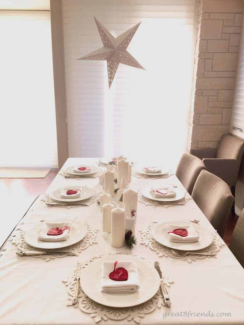 A Christmas white table setting with red glass heart place cards
