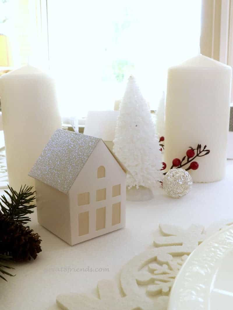 A Danish Christmas Dinner centerpiece all white with small house, fir tree, candles