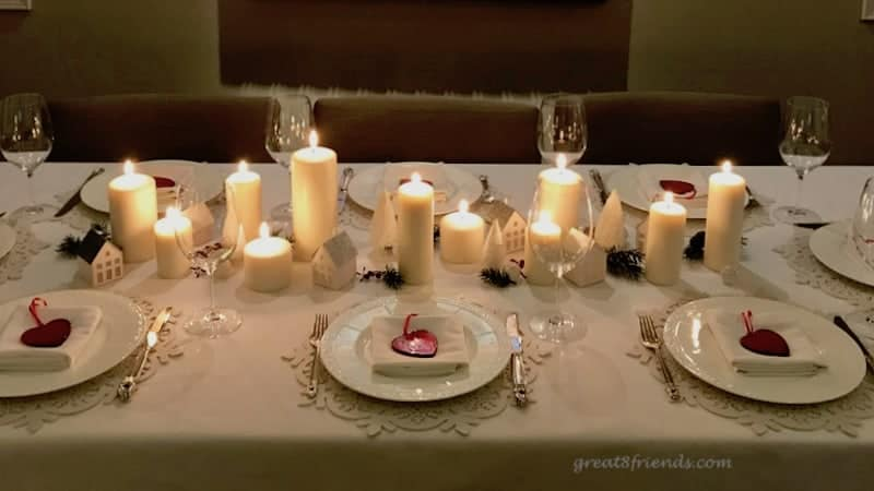Table set for Christmas with candles down the center, white plates with red glass hearts.