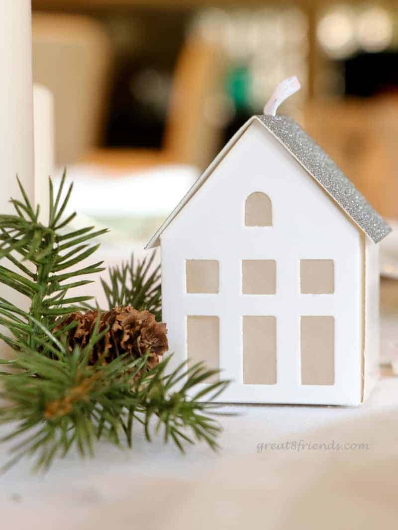 A  close up of small white paper house used in centerpiece