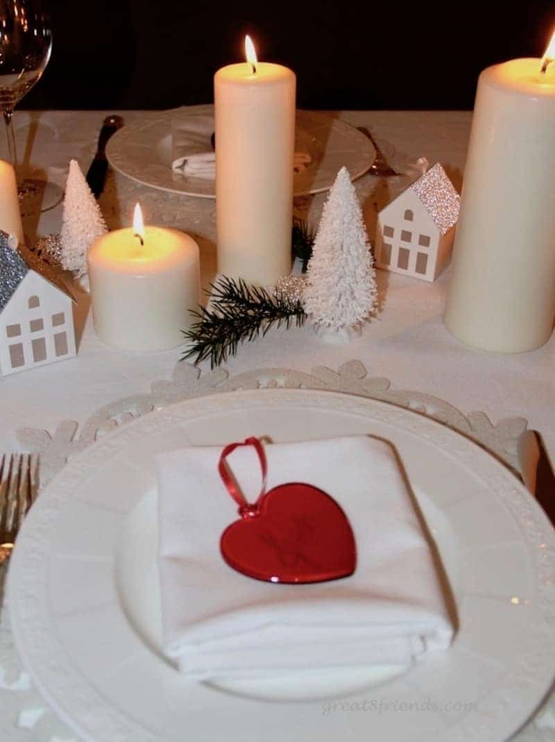 A Danish Christmas Dinner place setting with lit candles and small paper house and fir trees